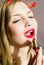 Closeup on seductive attractive sexual young blonde pinup woman draws red lipstick open lips sensually eyes closed Royalty Free Stock Photo