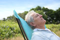 Closeup of senior man relaxing in long chair Royalty Free Stock Photo