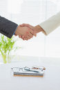 Closeup of shaking hands over eye glasses and diary Royalty Free Stock Image
