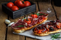 Closeup shot of an bruschetta with tomatoes salsa, parma, arugula and olives, close view Royalty Free Stock Photo