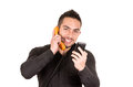 Closeup shot of handsome man using corded smiling phone and cell phone isolated on white Royalty Free Stock Images