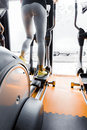 Closeup shot of legs of a female using elliptical trainer in gym Royalty Free Stock Photo