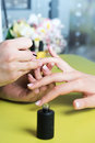 Closeup shot of a woman in a nail salon receiving a manicure by a beautician with nail file. Woman getting nail manicure. Beautici Royalty Free Stock Photo