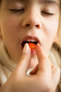 Closeup of sick girl putting pill on tongue Royalty Free Stock Photo