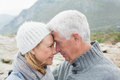 Closeup side view of a romantic senior couple together on rocky landscape Stock Images