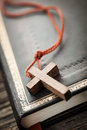 Closeup of simple wooden christian cross necklace on holy bible Royalty Free Stock Photo