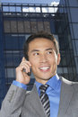 Closeup of smiling businessman using cellphone a young against building Royalty Free Stock Photos