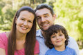Closeup of a smiling couple with son in park portrait the Stock Photography