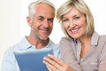 Closeup of a smiling mature couple using digital tablet portrait over white background Stock Images