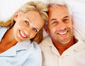 Closeup of a smiling senior couple lying on bed Stock Image