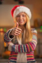 Closeup on smiling teenage girl in santa hat showing thumbs up christmas decorated kitchen Royalty Free Stock Photos