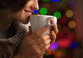 Closeup on smiling young woman with cup of hot chocolate marshmallow in front christmas lights Royalty Free Stock Image