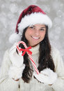 Closeup of smiling young woman holding a large candy cane Royalty Free Stock Photo
