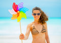 Closeup on smiling young woman holding windmill colorful toy Stock Photo