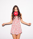 Closeup studio portrait of beautiful brunette girl blowing a red balloon wearing short cherry dress and spread her arms to the sid Royalty Free Stock Photo
