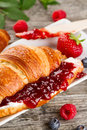 Closeup of tasty fresh appetizing croissants with fruit jam, cot