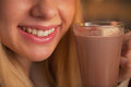 Closeup on teenage girl drinking cup of hot chocolate in kitchen Royalty Free Stock Images