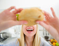 Closeup on teenager girl eating sandwich in the kitchen Royalty Free Stock Images
