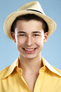 Closeup teenager wears hat and yellow shirt of happy on blue Royalty Free Stock Photography