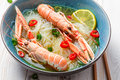 Closeup of thai soup with scampi and noodles on old wooden table Royalty Free Stock Photo