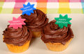 Closeup of three chocolate frosted cupcakes with Stock Photos