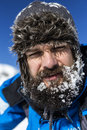 Closeup of tired man with snow on his beard wearing winter hat into the mountains Royalty Free Stock Photography