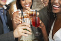 Closeup of toasting drinks at bar happy multiethnic couples the Royalty Free Stock Photo