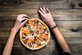 CLOSEUP Top view VERY HOT SLICED Italian Pizza with hand take a slice on wooden table with mushrooms, tomato, olives and