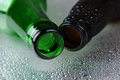 Closeup of two beer bottles on Wet Surface Royalty Free Stock Images