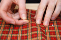 Closeup of two hands pinning red plaid fabric sticking pins into festive Royalty Free Stock Photo