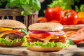Closeup two homemade hamburgers made fresh vegetables old wooden table Royalty Free Stock Photography