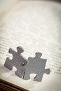 Closeup of Two Jigsaw Puzzle Pieces on Page of a Book Royalty Free Stock Photo