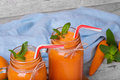 Closeup of two mason jars full of carrot smoothie with basil, sappy mint and carrot on a light blurred background. Royalty Free Stock Photo