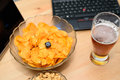 Closeup of unhealthy snack and beer with laptop in background stock photo Stock Photography