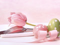Closeup of utensils and pink tulip on pink background Stock Photo