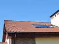 Closeup of Vacuum Solar Water Heating System Rain Gutter on the Red Tiled House Roof Royalty Free Stock Photo