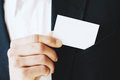 Closeup view of Businessman takes out a blank white business card from his jacket pocket.Horizontal mockup, blurred Royalty Free Stock Photo