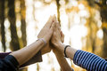 Closeup view of four people joining their hands together high up in the air outside in a forested area Royalty Free Stock Image