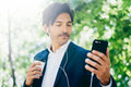Closeup view of Handsome smiling businessman using smartphone for listining music while walking in city park.Young man Royalty Free Stock Photo