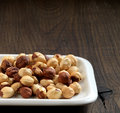 Closeup view of hazelnuts on white plate and brown wood table Royalty Free Stock Photography