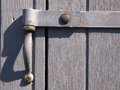 Closeup view of an old metal hinge vintage on a gray wooden door Stock Images