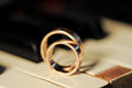 Closeup of wedding rings on piano Stock Photo