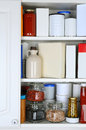 Closeup of a well stocked pantry one door the cabinet is open revealing canned goods condiments package foodstuffs and storage Stock Photos