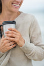 Closeup on woman on beach with cup of hot beverage happy young cold Royalty Free Stock Photography
