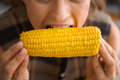Closeup of woman biting into fresh crunchy sweet corncob the crunch is perfect the sweetness even better and the flavor is so rich Stock Photography