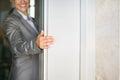 Closeup on woman hand holding elevator door