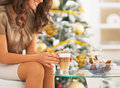 Closeup on woman having latte macchiato near christmas tree and candies Royalty Free Stock Photos