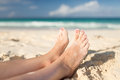 Closeup of woman legs on sea shore summer beach leisure and body part concept Stock Photos