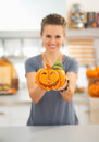 Closeup on woman showing ceramic halloween pumpkin in kitchen ready to invasion smiling young decorated Royalty Free Stock Images