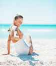 Closeup on woman sitting on beach and playing with sand smiling young in swimsuit Royalty Free Stock Images